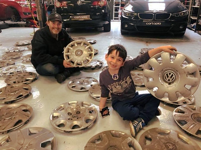 A young boy who is ecstatic with his wide variety of hubcaps
