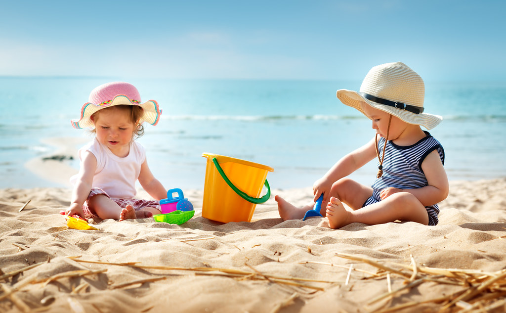 Two children play on beach with a bucket