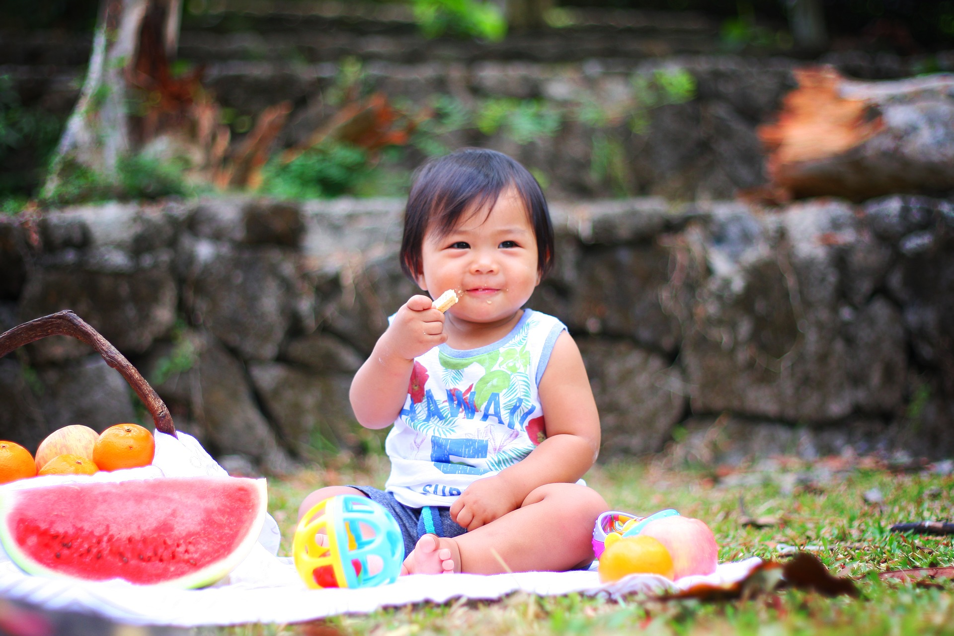 Small child snacking on fruit at a picnic
