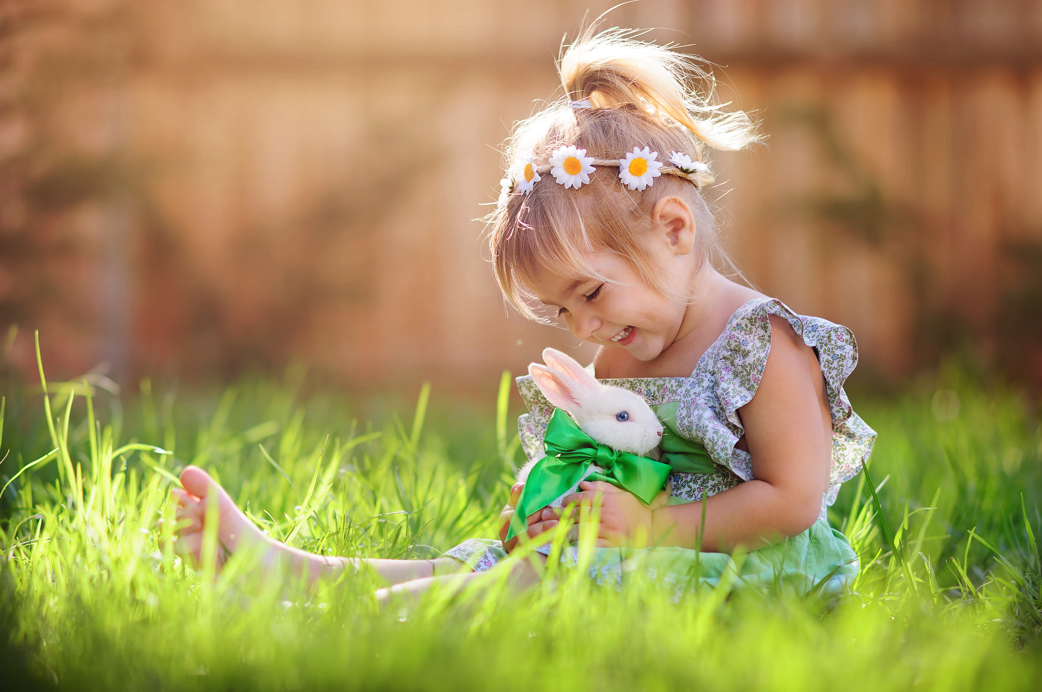 A young girl with flowers in her hair sits in sun with her pet rabbit
