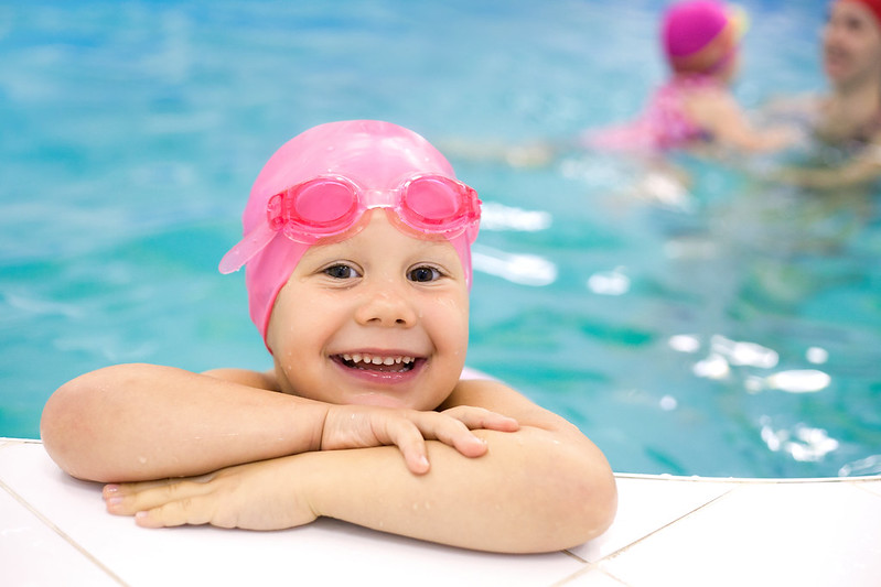 Young girl in pool, smiling, with pink cap