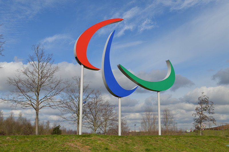 The Paralympic logo, featuring a red, blue and green curve, standing on a green hill