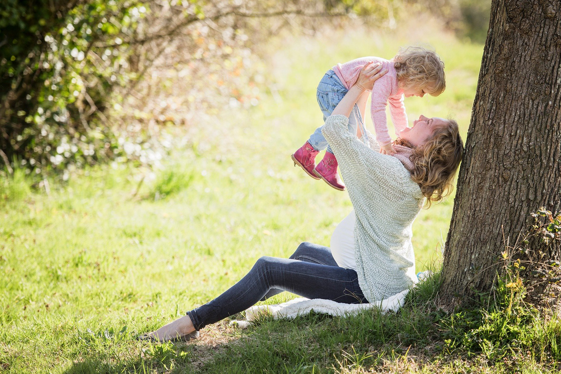A mother raises her small daughter into the air, while sat beneath a tree in summer time.