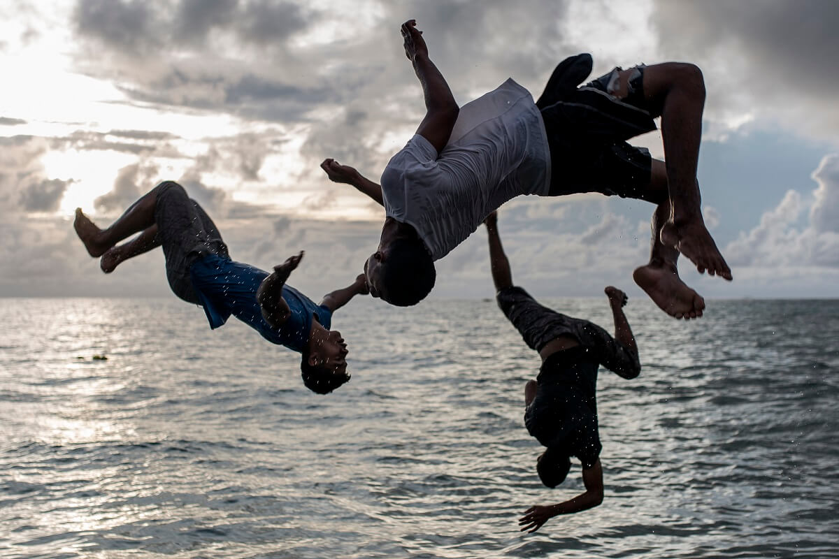 image of teenagers jumping into water