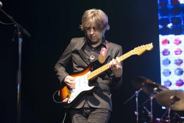 Eric Johnson tient sa guitare en position haute
