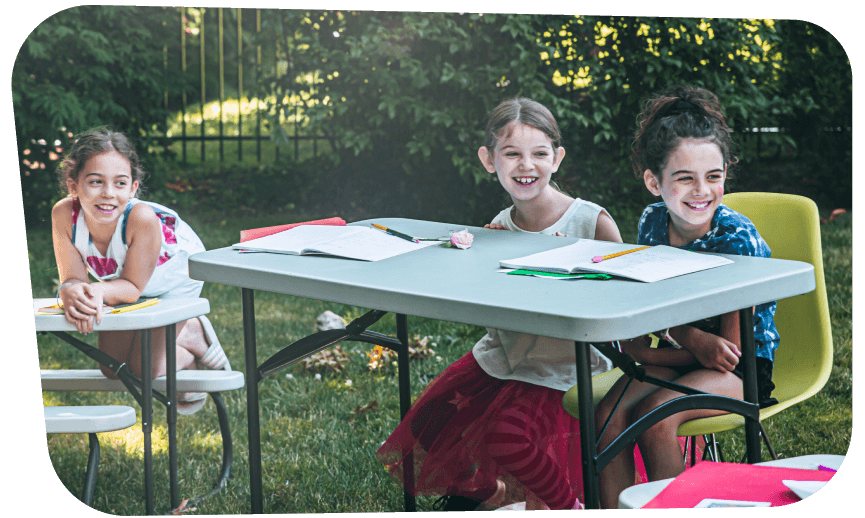 Three girl students sitting at tables outside in their backyard pod