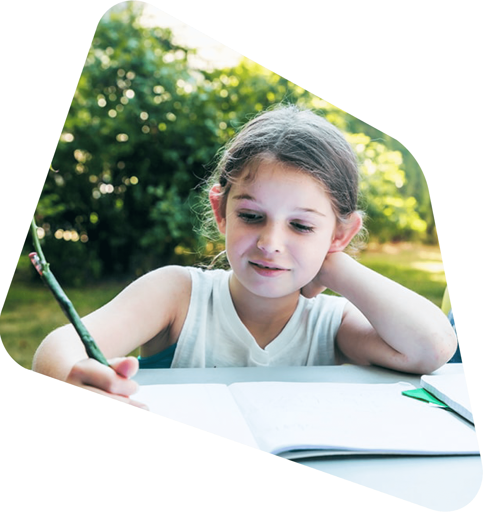 Young girl sitting outside practicing her handwriting with a flower pen