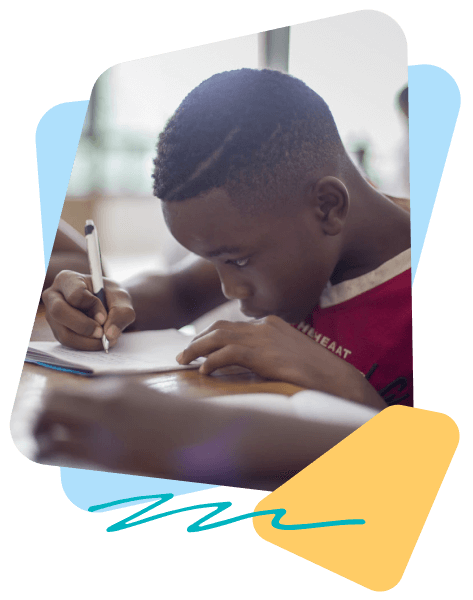 Boy in red shirt practicing his handwriting in English block