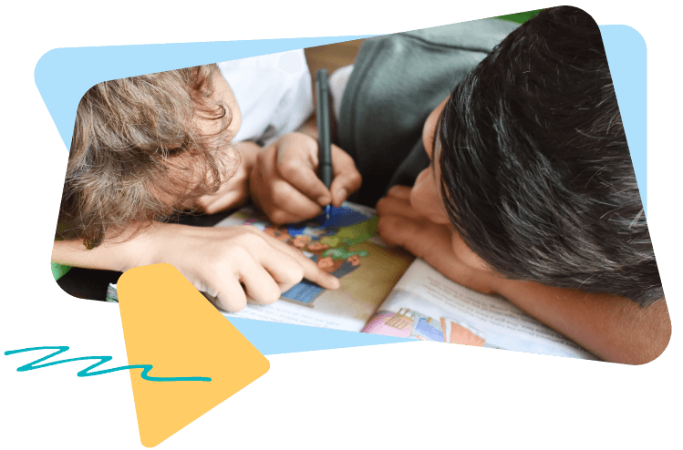 Two boys with their heads down working together on their workbook