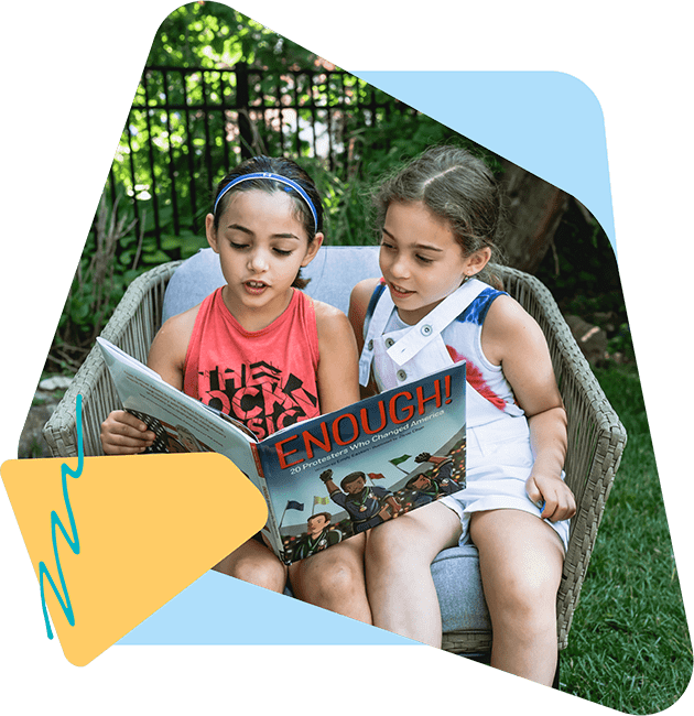 Two young girls with dark hair sitting outside in a chair together reading a book.