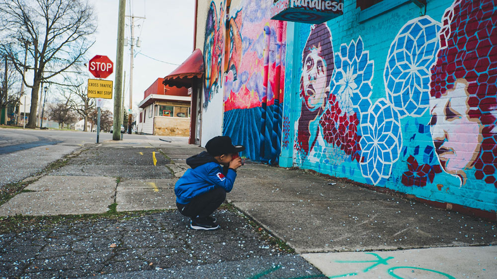 Child taking photo of mural