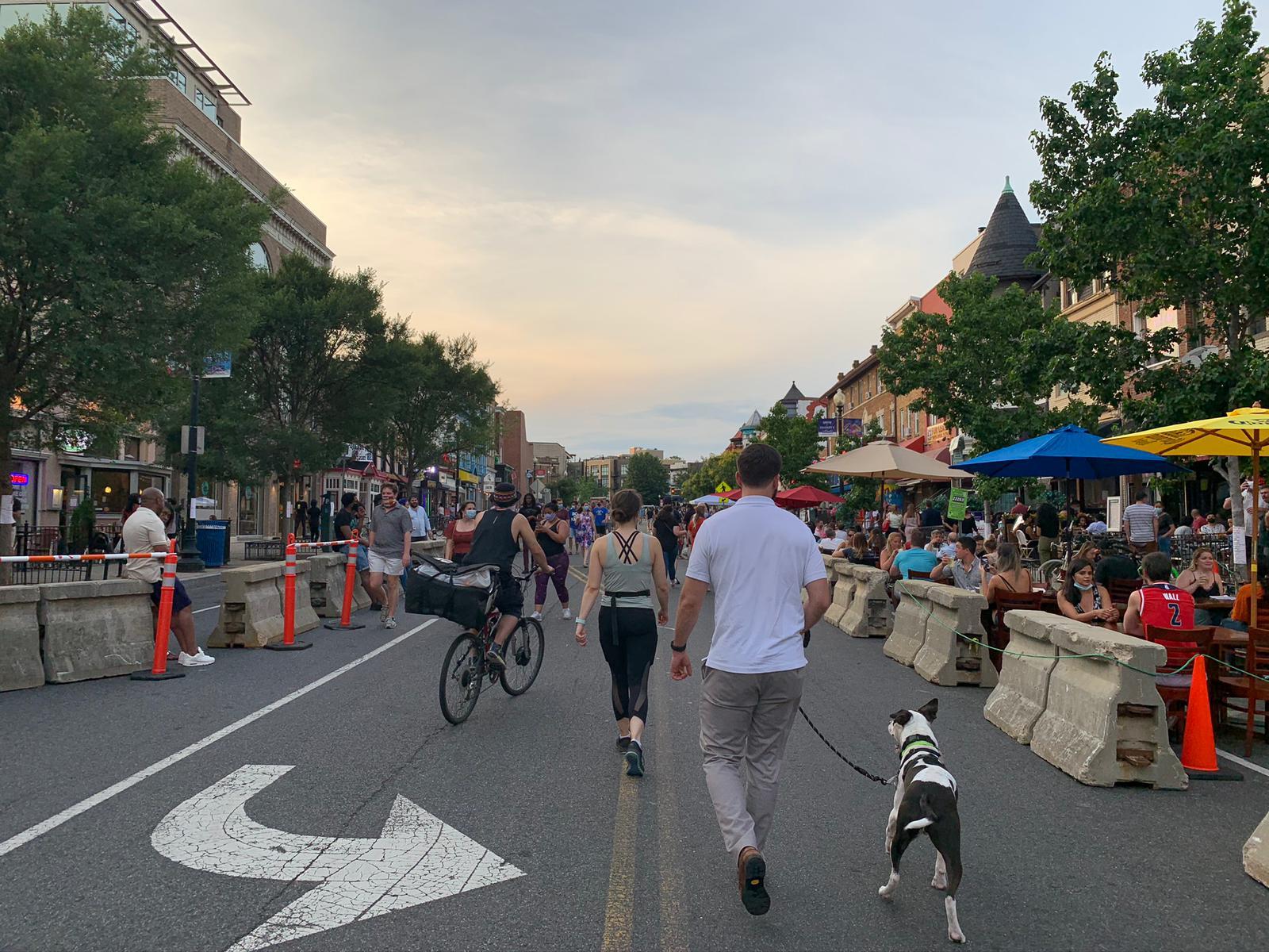 People walking dog down street alongside outdoor restaurant