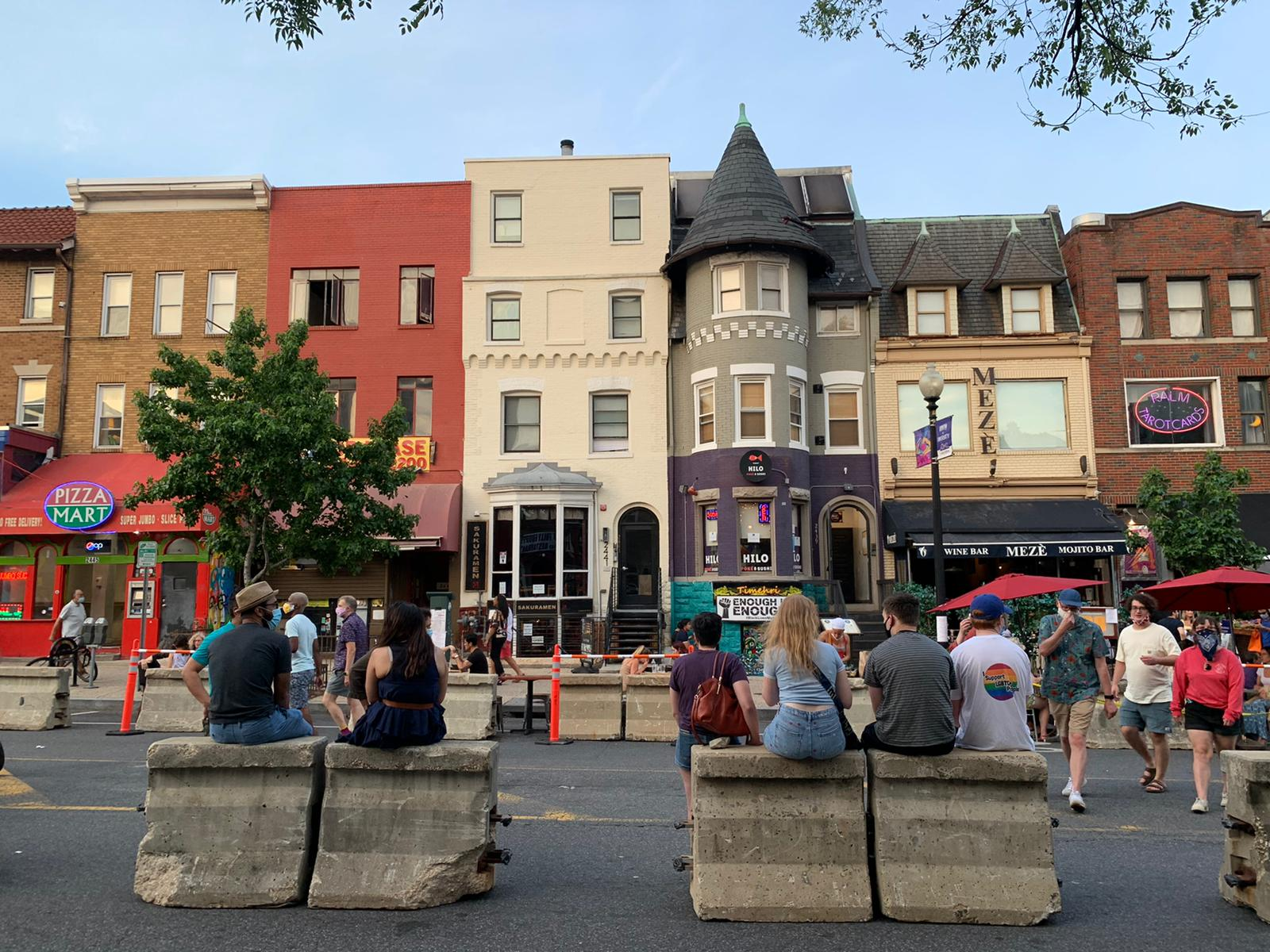 People sitting on concrete barriers alongside outdoor restaurant