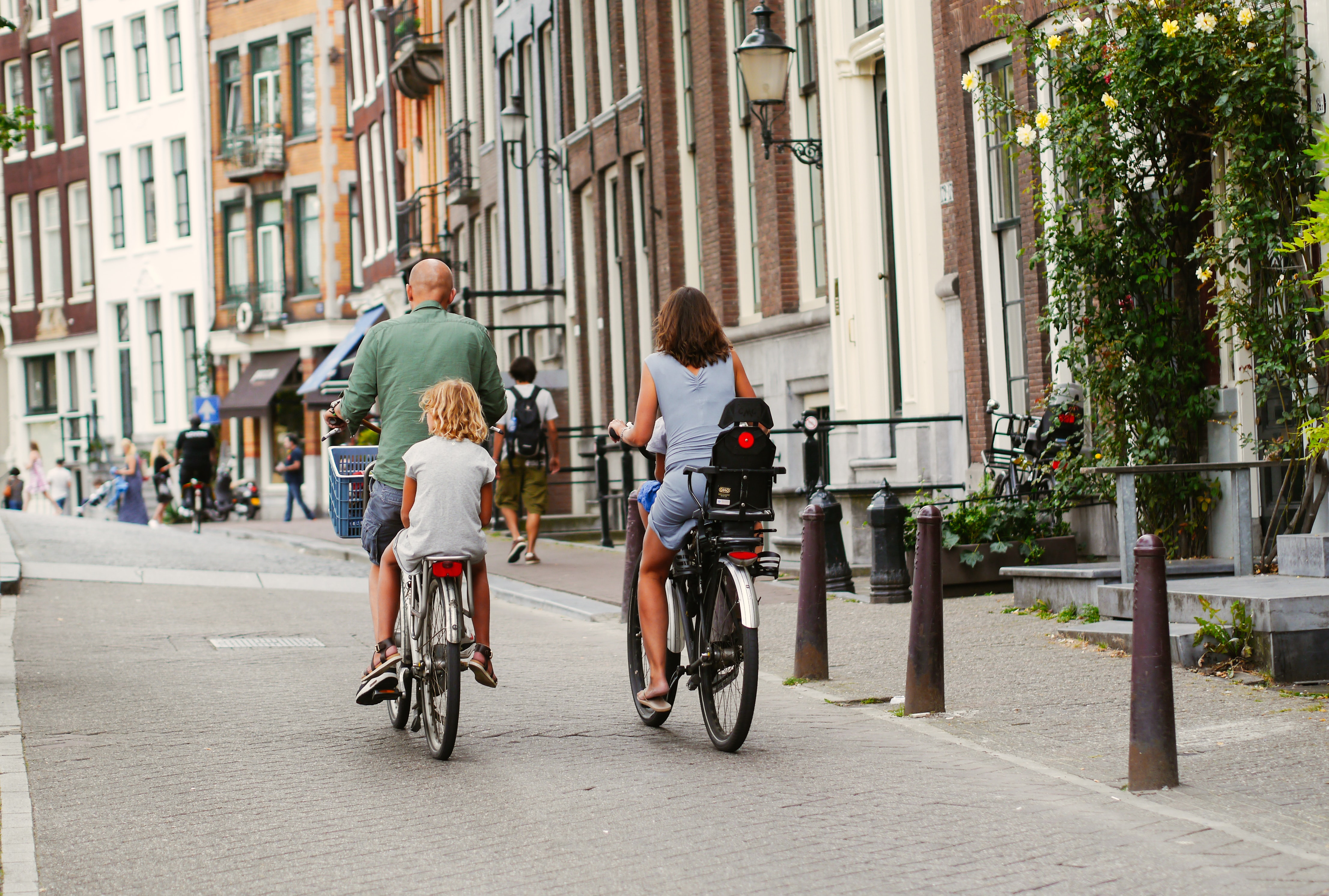 Picture of people riding their bikes down the street. The bikers are riding away from the camera and have children in bikeseats.
