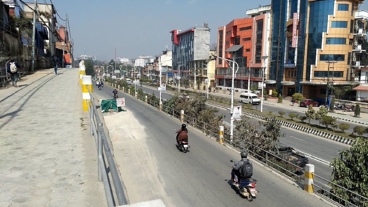 Motorists on two-wheelers driving on a nearly empty road