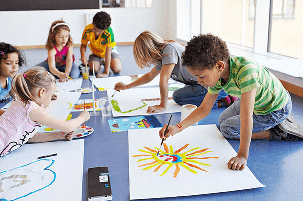 A group of six kids sitting together on the floor painting on their own white poster board.