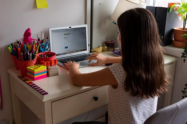 Young girl with dark hair sitting at desk facing computer screen.