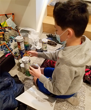 A young boy sitting on the floor organizing and counting food cans