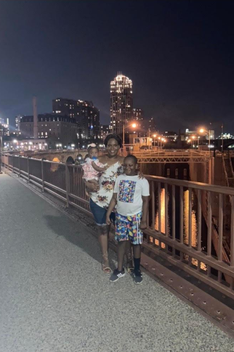 A woman standing on a bridge, holding a young child and standing next an older child with her hand on his sholder, with night sky and city lights in the background.