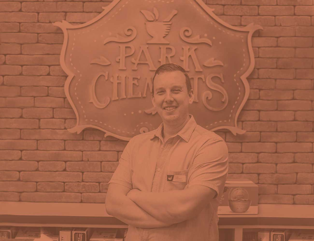 Gary Valevich (Pharmacist/Owner) smiling in front of the Park Chemists sign