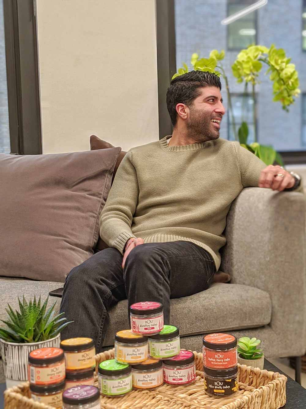 BOU Brands co-founder Kunal Kohli sitting on a couch, smiling, and looking away [Unioncrate]