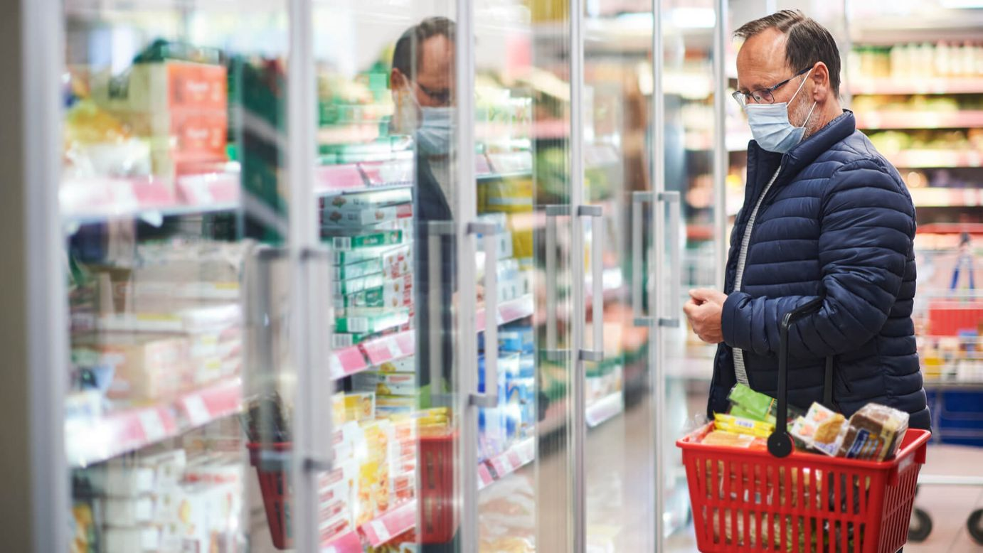 A consumer with a full shopping basket browsing the frozen aisle [Unioncrate]