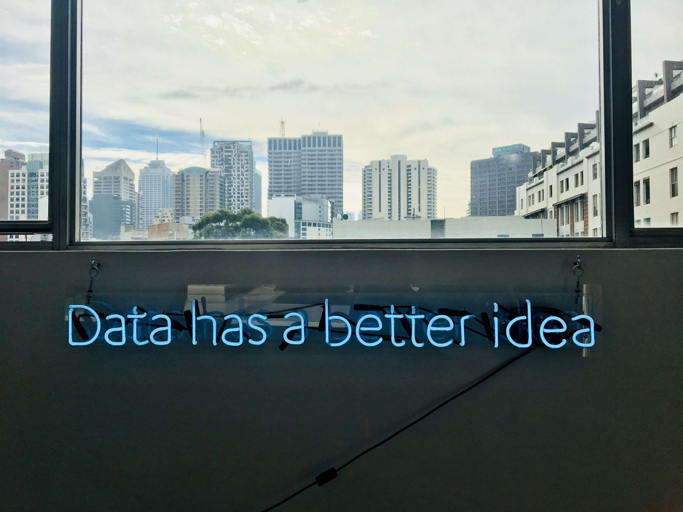 """Window to a city scene with a blue neon sign that says """"Data has a better idea"""" [Unioncrate]"""