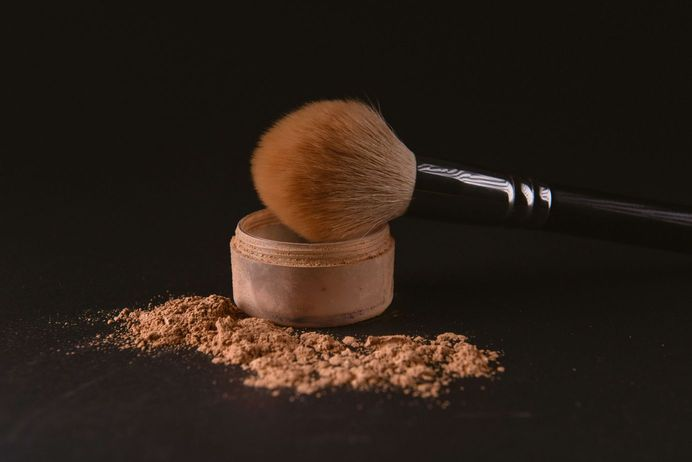 Face makeup and cosmetic brush against a black background [Unioncrate]