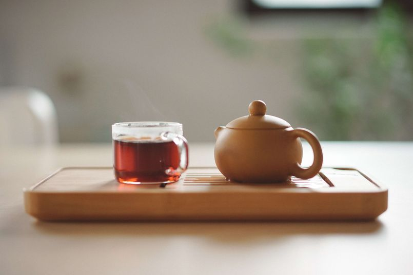 Teapot and a cup of tea on a wooden platter [Unioncrate]