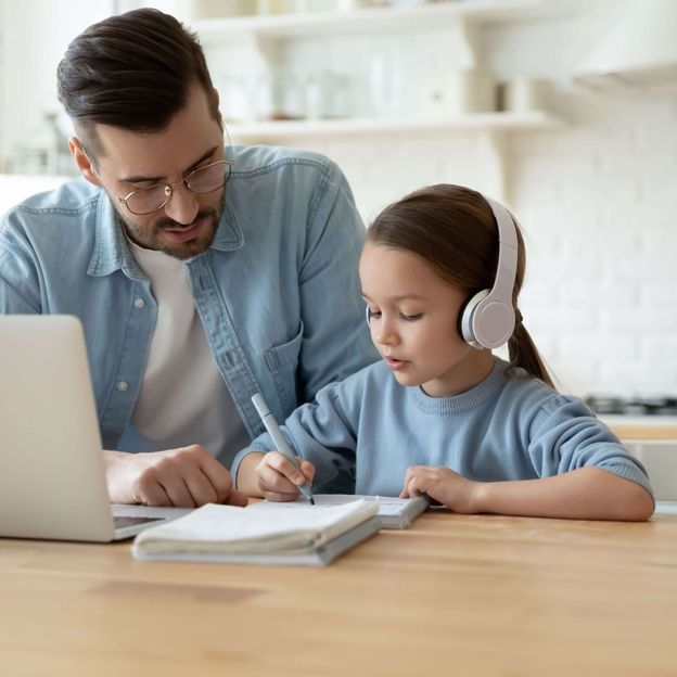 Parent helping their child with school work. Both wear light blue and the child has a pair of headphones [Unioncrate]