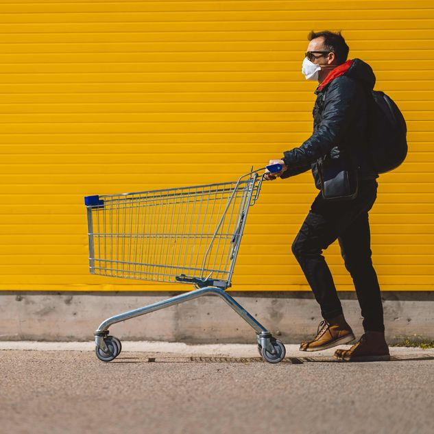 Masked consumer pushing retail shopping cart against a yellow background [Unioncrate]