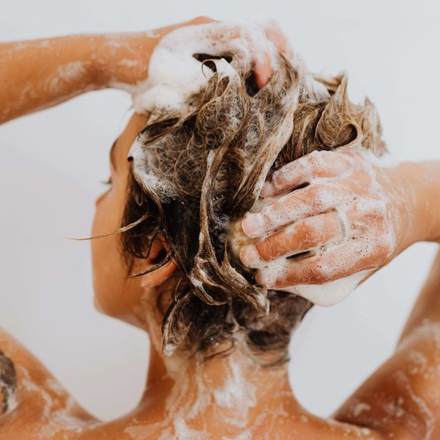 A person lathering their hair with shampoo, representing the shampoo category for Unioncrate's CPG Year In Review