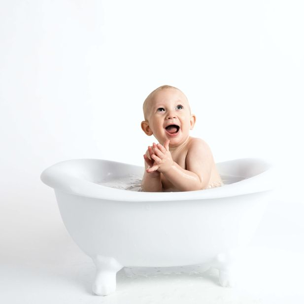A smiling baby sitting in a white bathtub, representing the baby bath products category for Unioncrate's CPG Year In Review