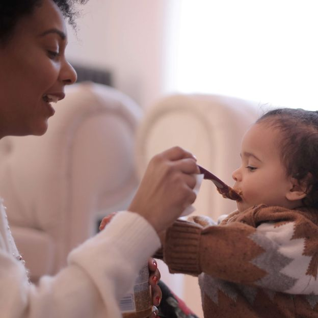 A smiling parent feeding their child, representing the baby and toddler food category for Unioncrate's CPG Year In Review