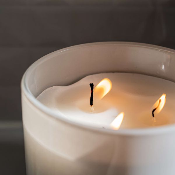 Lit white candle with two wicks, representing the scented candles category for Unioncrate's CPG Year In Review