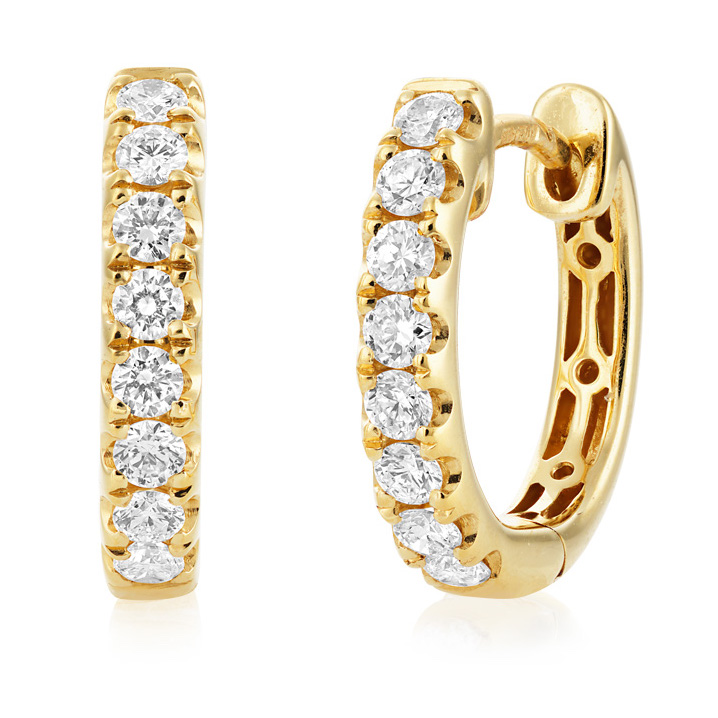 Dainty, round, brilliant-cut diamond huggie, hoop earrings in a simplistic claw setting in solid 18ct yellow gold with a secure catch for extra safety. Equivalent size to scale as 5p!
