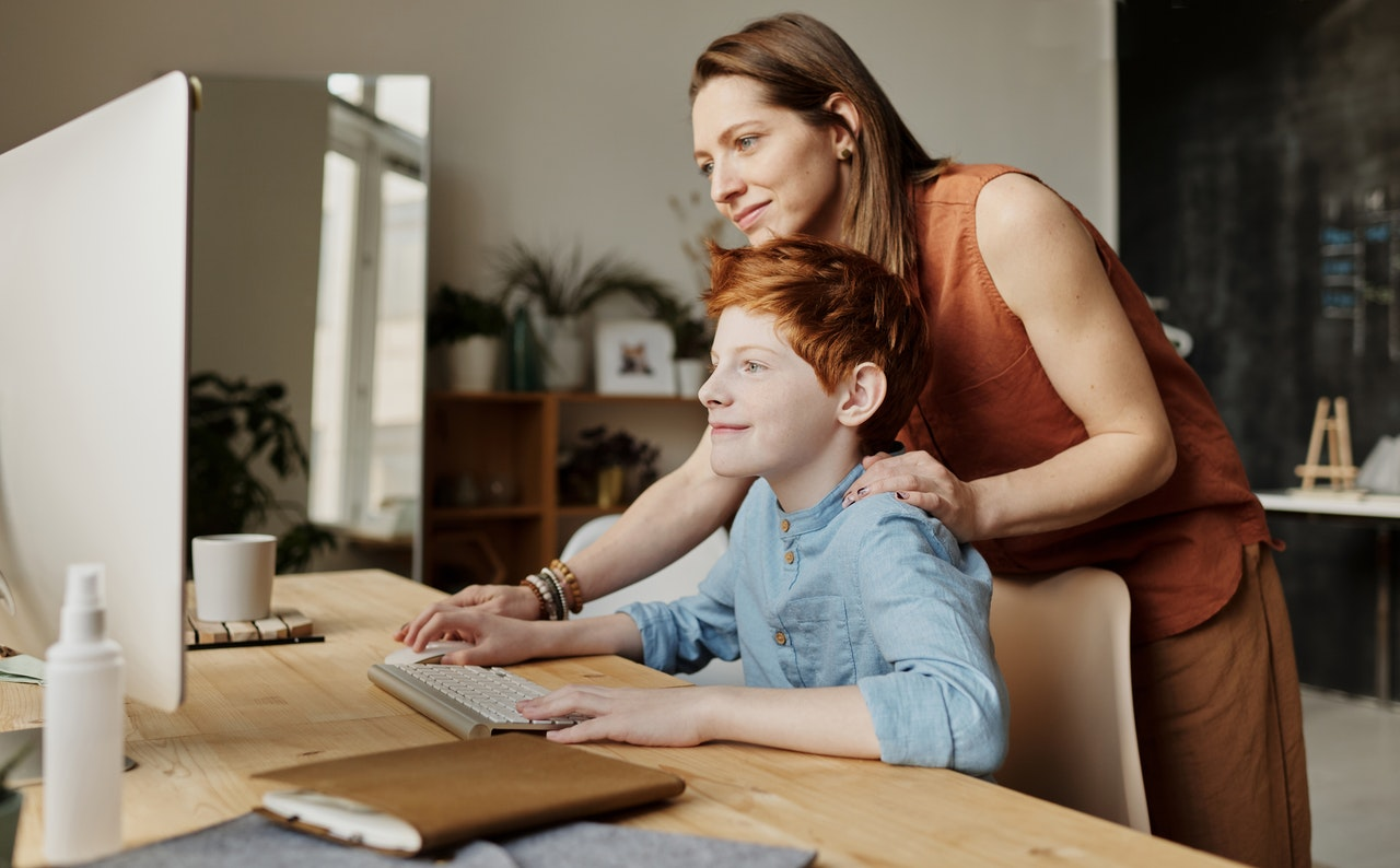 Mother helping son use the computer.