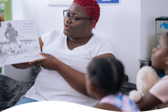 tiney childminder Alicia Smith reading a book to children