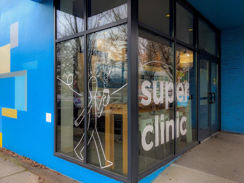 """A window decal that reads """"super clinic."""""""