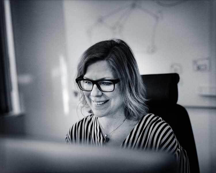 Woman working at a desk with a monitor in the foreground