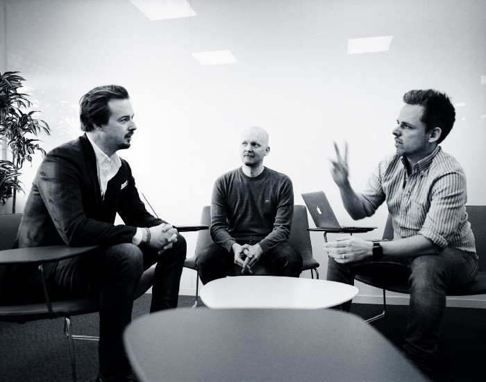 Three men sitting at a table speaking