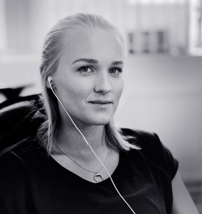Woman with headphone in ear smiling