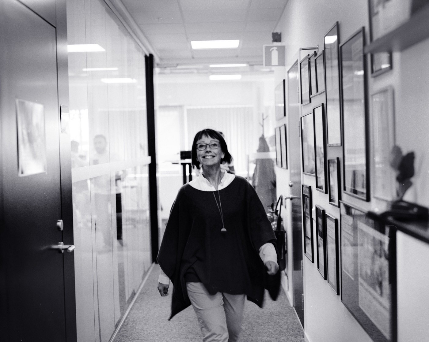 Happy woman walking towards the camera in an office.