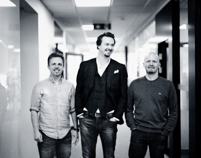 Three men standing side by side in their office