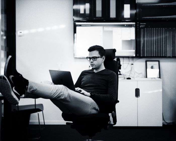 Man sitting with his feet on his desk working with his laptop in his knee
