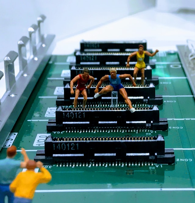 Small human figurines running a hurdle-race over computer parts
