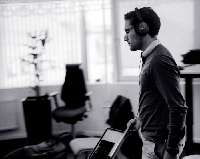 Guy with headphones standing in an office
