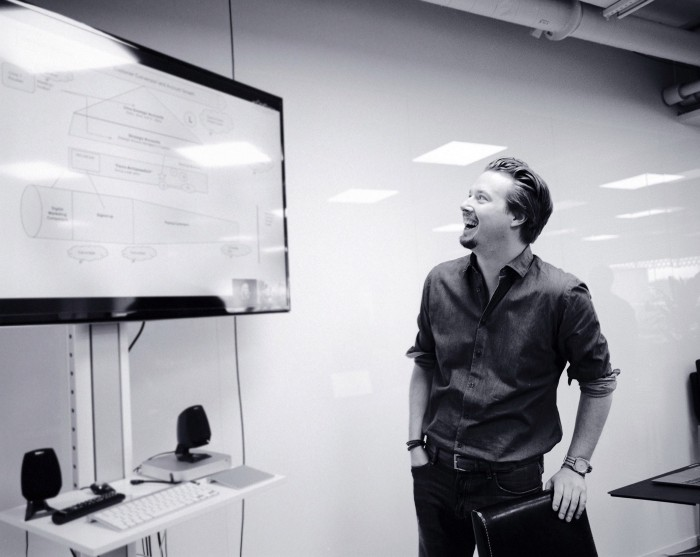 Person standing by screen, presenting and laughing
