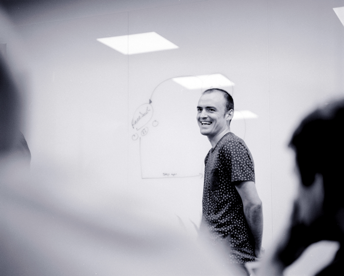 Smiling person standing by a white board
