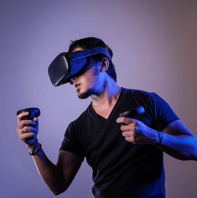 Gamer with VR headset and controllers playing